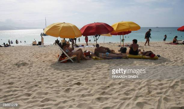 This picture taken on 10 March 2007 shows tourists sunbathing at Doctor Cave beach in Montego Bay Jamaica is the third largest island in the...