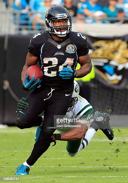 Montell Owens of the Jacksonville Jaguars attempts to run past Yeremiah Bell of the New York Jets during the game at EverBank Field on December 9...