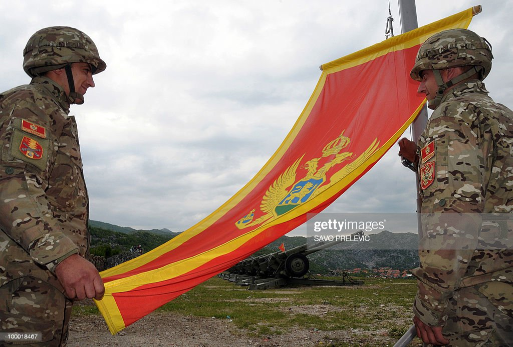 Montenegrin Army soldiers fire artillery look at the Montenegro flag during preparations on the eve of Independence day, on May 20, 2010 in Cetinje. Montenegro, a former Yugoslav Republic with a population of around 650,000, split away from a loose union with Serbia four years ago after a historic independence referendum. AFP PHOTO / Savo PRELEVIC