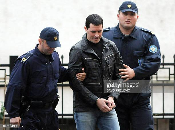 Montenegrin police officers escort Vladimir Lekic member of the 'Pink Panther' gang of international jewelry thieves to the High Court in Podgorica...