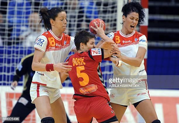 Montenegro's pivot Ana Dokic is pushed by Spain's Begona Fernandez and Veronica Cuadrado during the 2012 EHF European Women's Handball Championship...