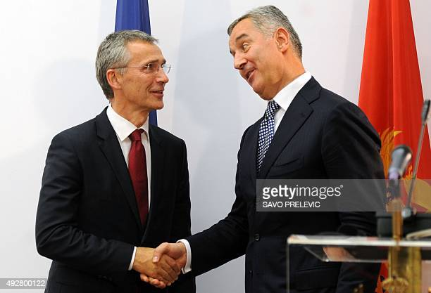 Montenegro's Prime Minister Milo Djukanovic shakes hands with NATO Secretary General Jens Stoltenberg after a joint press conference on October 15...