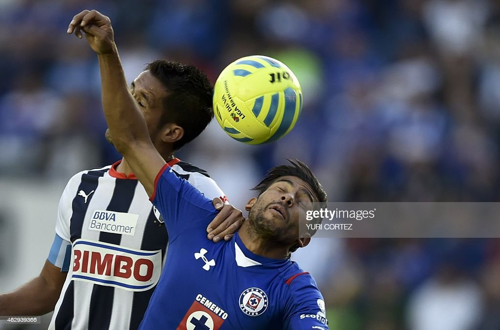 Monterrey's defender Severo Meza jumps for the ball with Cruz Azul's midfielder Joao Rojas during their Clausura tournament football match at the...