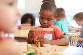 Montessori Pupil Working At Desk With Wooden Shapes
