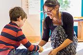 Montessori teacher helping student in classroom