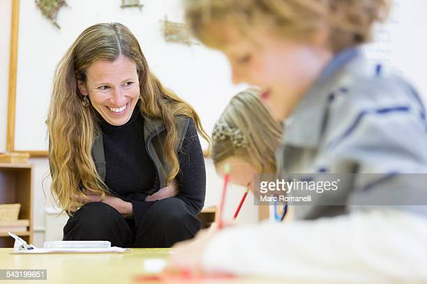 Montessori teacher helping students in classroom