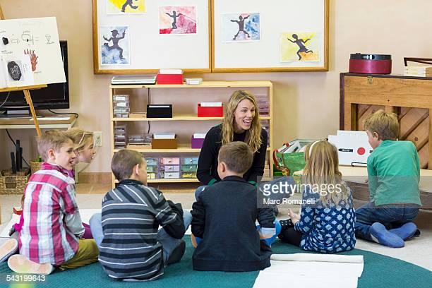 Montessori teacher talking to students in classroom