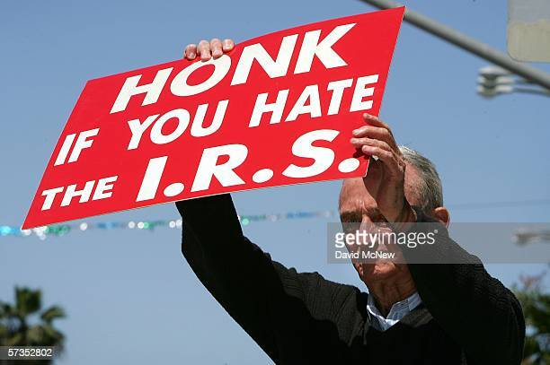J D Montgomery holds a sign on the street outside of the James C Corman Federal Building encouraging motorist to express their anger at the Internal...