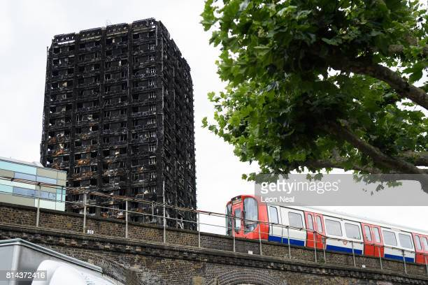 A month after a massive fire claimed the lives of at least 80 people the remains of Grenfell Tower are seen as a London Underground train passes by...