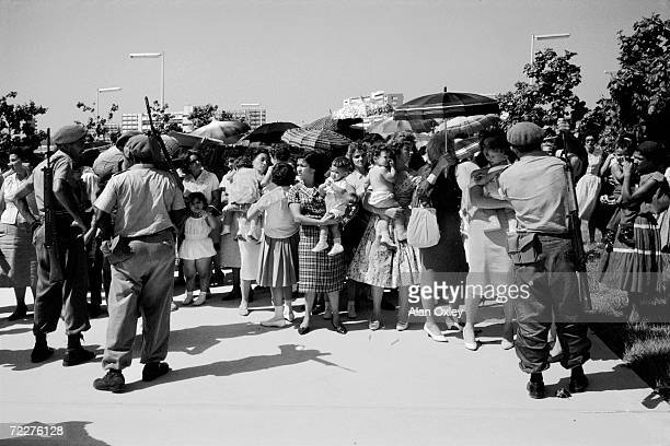 A month after the April 1961 Bay Of Pigs invasion armed militia men control a crowd of mothers wives and children of POWs captured by Castro forces...