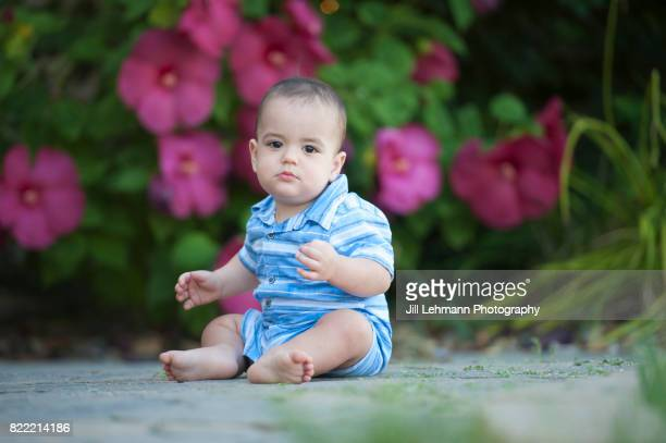 12 month Beautiful Baby Sits on Concrete with Flowers