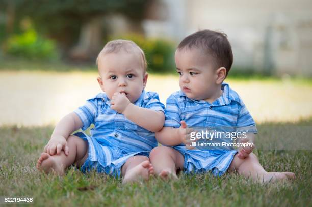 12 month Beautiful Fraternal Twin Babies Sit in the Grass Together