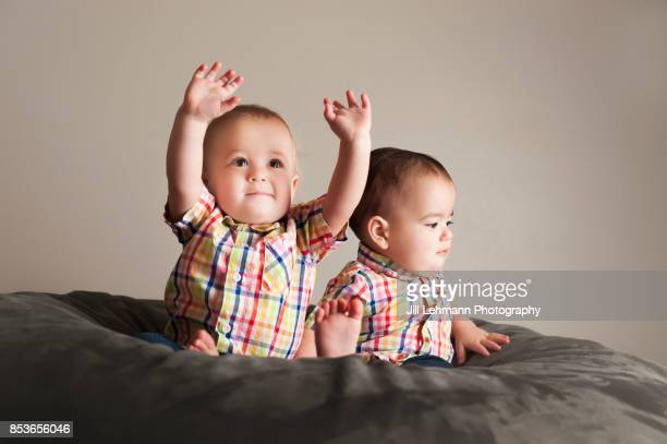 12 month Fraternal Twin Boys Play Together On Their Backs on a Bean Bag - One Boy is Excited