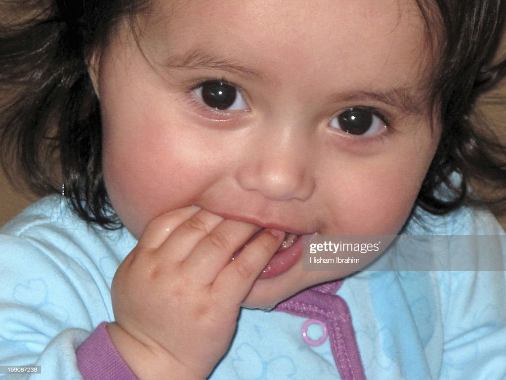 7 month old cute baby girl biting fingers : Stock Photo
