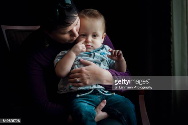 12 Month Old Fraternal Twin is embraced by Mother in a Formal Portrait