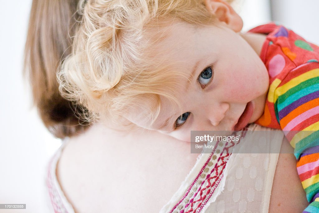 18 month old girl resting on her mother's shoulder : Stock Photo