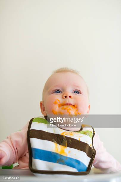 6 month old girl with food on her face.