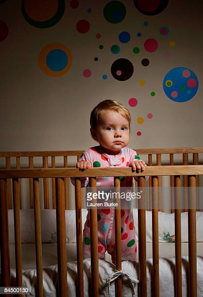 11 month old infant standing in crib at night
