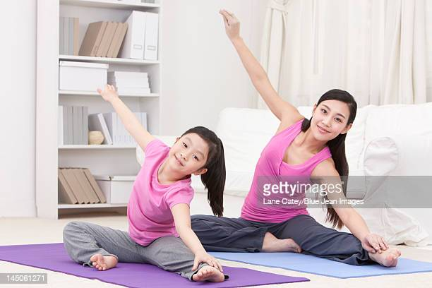 Monther and daughter doing yoga