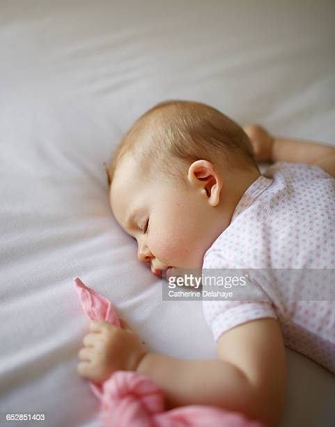 A 7 months old baby sleeping on a bed