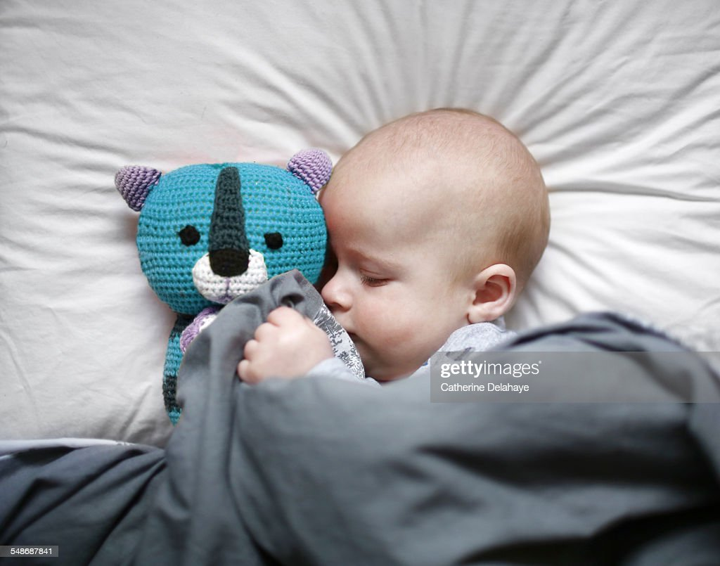 A 6 months old baby sleeping with his cuddly toy