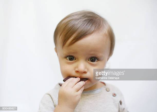 A 18 months old boy eating chocolate