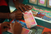 Monti Young fills out her Powerball numbers as she buys a ticket at Circle News Stand on November 28 2012 in Hollywood Florida The jackpot for...