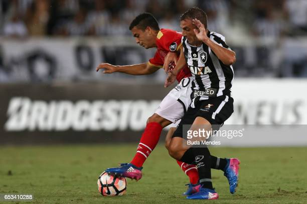 Montillo of Botafogo struggles for the ball with Lucas Rodrguez of Estudiantes during a match between Botafogo and Estudiantes as part of Copa...