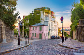 Cozy old street with pink house at the sunny sunrise, quarter Montmartre in Paris, France