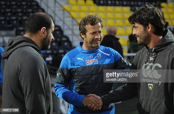 Montpellier coach Fabien Galthie shakes hands with La Rochelle's threequarters' coach Xavier Garbajosa next to coach Patrice Collazo before the start...