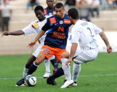 Montpellier midfielder Younes Belhanda vies with Boulogne defender Nicolas Rabuel and midfielder Olubayo Adefemi during their French L1 football...