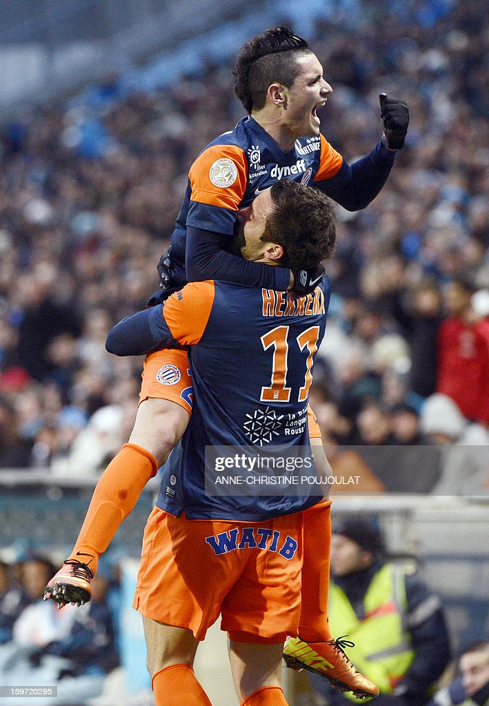 Montpellier's Argentinian forward Emmanuel Herrera (Down) is congratulated by Montpellier's French midfielder Remy Cabella (Top) after scoring a goal on January 19, 2013 at the Velodrome stadium in Marseille, southern France, during the French L1 football match Marseille vs Montpellier. AFP PHOTO / ANNE-CHRISTINE POUJOULAT