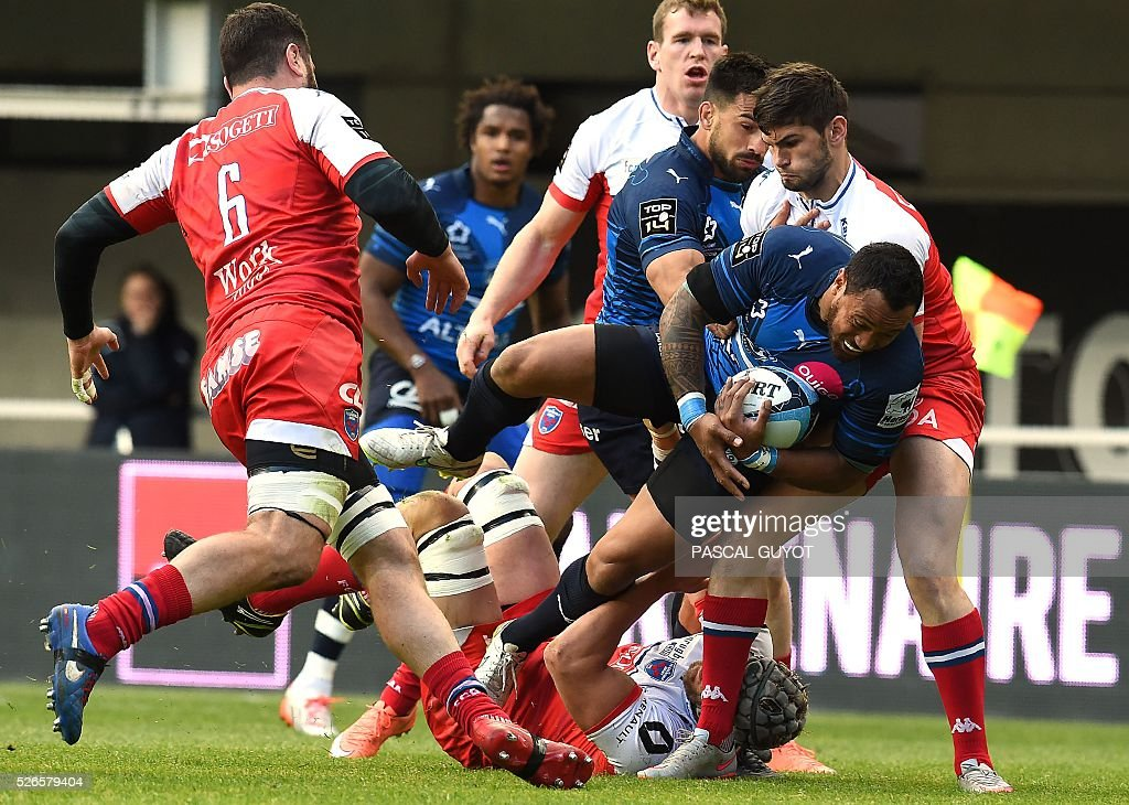 Montpellier's centre Anthony Tuitavake from New Zealand (C) vies with Grenoble's French flanker Jonathan Best (L) and Grenoble's French flyhalf Gilles Bosch (R) during the French Top 14 rugby union match between Montpellier and Grenoble on April 30, 2016 at the Altrad stadium in Montpellier, southern France.
