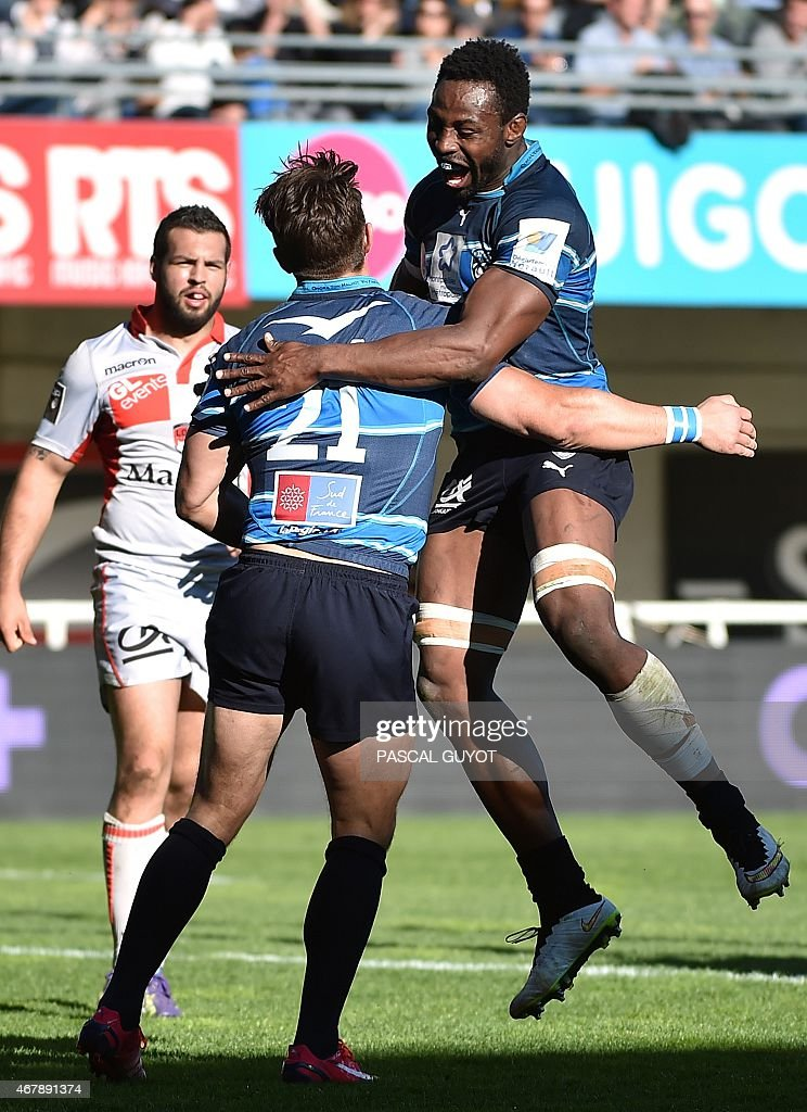 Montpellier's flanker Fulgence Ouedraogo (R) and Montpellier's centre Wynand Olivier (L) react after scoring a try during the French Top 14 rugby union match between Montpellier and Lyon on March 28, 2015 at the Altrad stadium in Montpellier, south of France. AFP PHOTO / PASCAL GUYOT