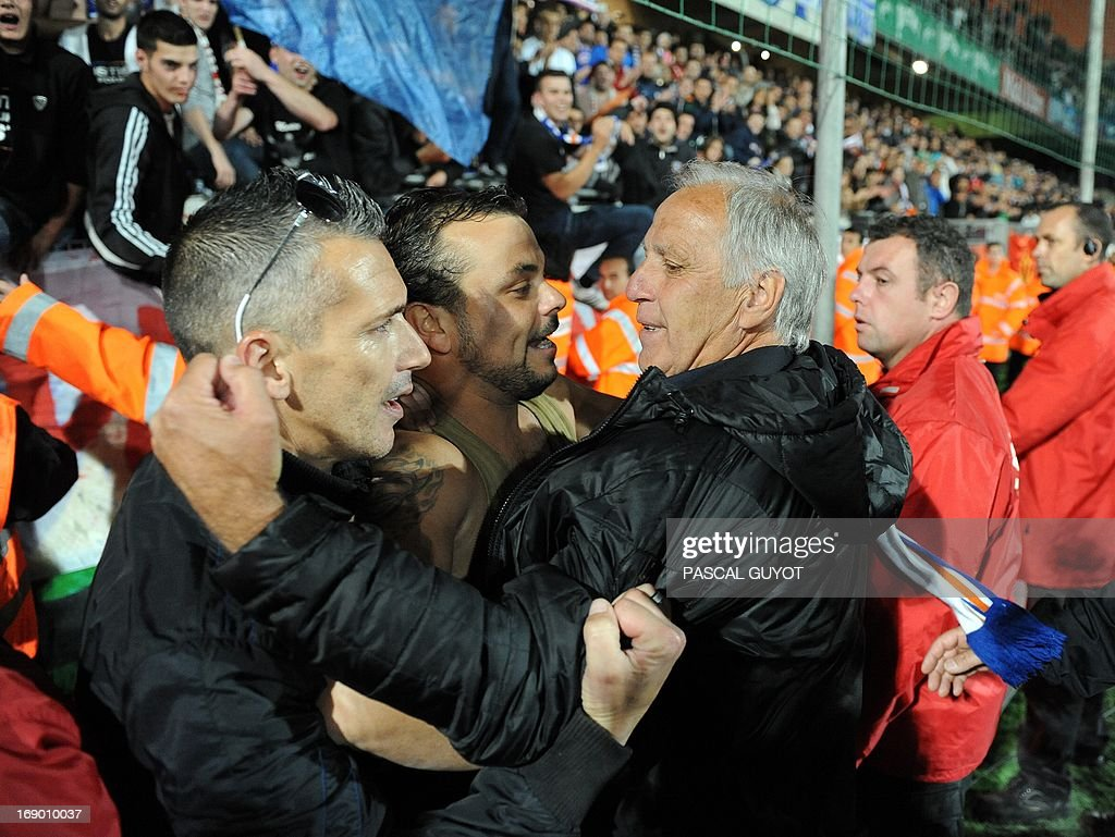Montpellier's French coach Rene Girard (R) greets a man after the French L1 football match Montpellier vs Lille on May 18, 2013 at the Mosson stadium in Montpellier, southern France. The match ended in a 0-0 draw.