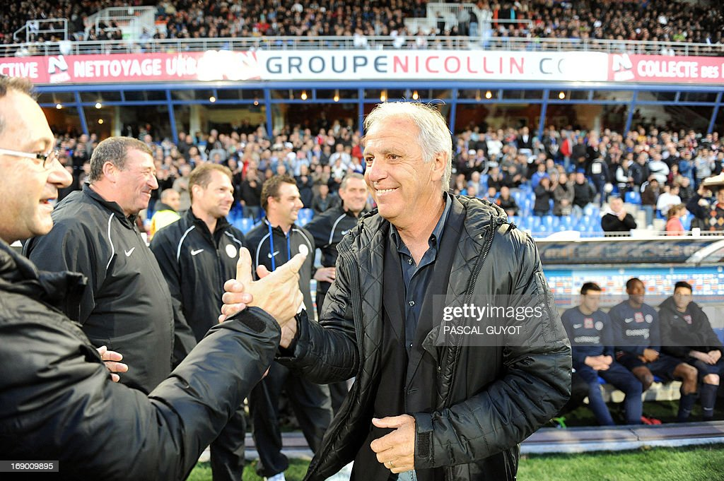 Montpellier's French coach Rene Girard shakes hands with an unidentied man during the French L1 football match Montpellier vs Lille on May 18, 2013 at the Mosson stadium in Montpellier, southern France. The match ended in a 0-0 draw.