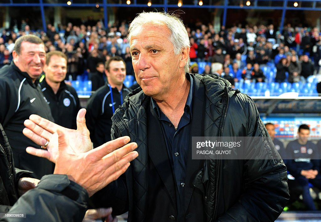 Montpellier's French coach Rene Girard shakes hands with an unidentied man during the French L1 football match Montpellier vs Lille on May 18, 2013 at the Mosson stadium in Montpellier, southern France. The match ended in a 0-0 draw. AFP PHOTO / PASCAL GUYOT