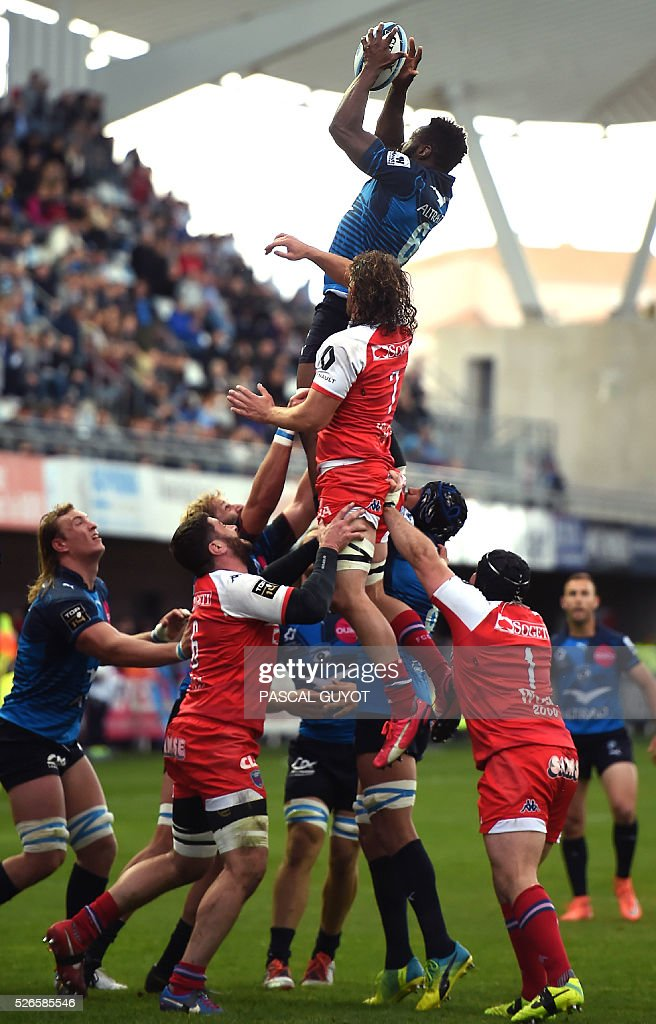 Montpellier's French flanker Fulgence Ouedraogo (top) grabs the ball in a line out during the French Top 14 rugby union match between Montpellier and Grenoble on April 30, 2016 at the Altrad stadium in Montpellier, southern France.