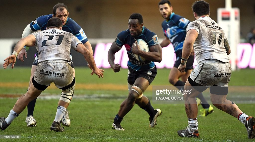 Montpellier's French flanker Fulgence Ouedraogo (C) runs with he ball during the French Top 14 rugby union match between Montpellier and Stade Toulousain at the Altrad Stadium in Montpellier, southern France, on December 20, 2014. AFP PHOTO / PASCAL GUYOT