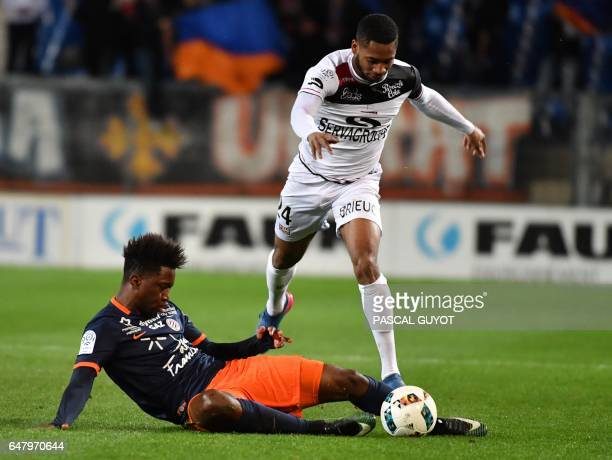 Montpellier's French forward Isaac Mbenza vies with Guingamp's French defender Marcus Coco during the French L1 football match between MHSC...