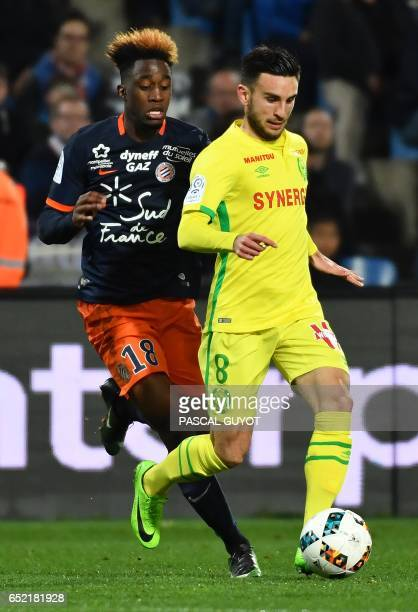 Montpellier's French forward Isaac Mbenza vies with Nantes' French midfielder Adrien Thomasson during the French L1 football match between MHSC...