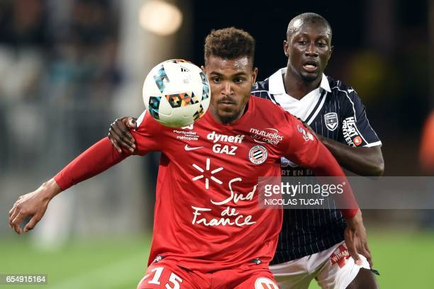 Montpellier's French forward Steve Mounie vies with Bordeaux's French defender Youssouf Sabaly during the French L1 football match between Bordeaux...