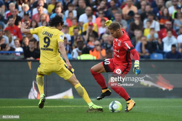 Montpellier's French goalkeeper Benjamin Lecomte defends against Paris SaintGermain's Uruguayan forward Edinson Cavani during the French Ligue 1...