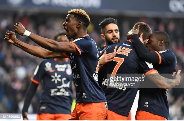 Montpellier's French midfielder Paul Lasne is congratulated by teammates after scoring a goal during the French L1 football match between MHSC...