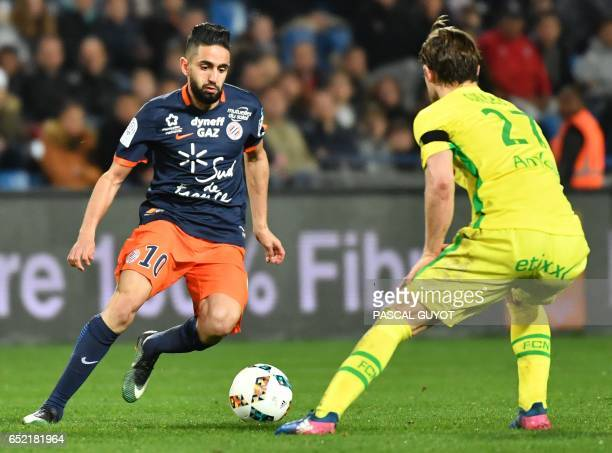 Montpellier's French midfielder Ryad Boudebouz vies with Nantes' Belgian midfielder Guillaume Gillet during the French L1 football match between MHSC...