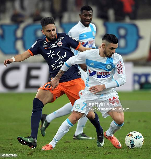 Montpellier's French midfielder Ryad Boudebouz vies with Olympique de Marseille's French midfielder Remy Cabella after scoring a goal during the...