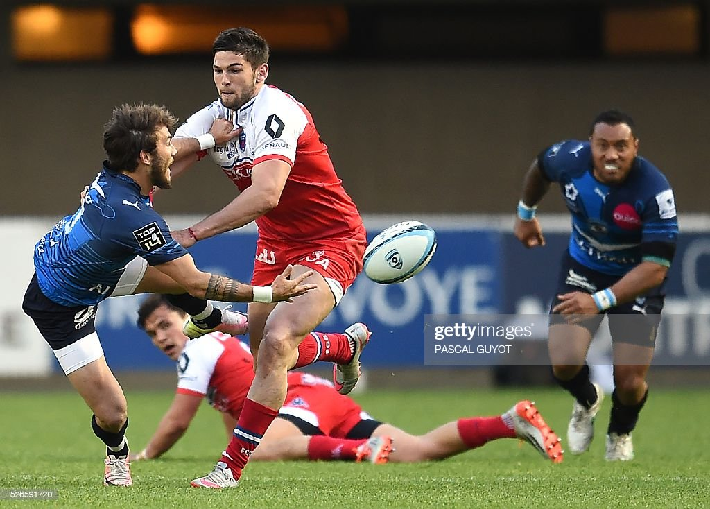 Montpellier's French scrumhalf Benoit Paillaugue (L) passes the ball during the French Top 14 rugby union match between Montpellier and Grenoble on April 30, 2016 at the Altrad stadium in Montpellier, southern France.