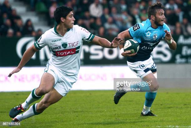Montpellier's French scrumhalf Benoit Paillaugue runs with the ball next to Pau's French scrumhalf Thibault Daubagna during the French Top 14 rugby...