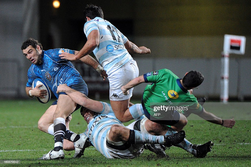 Montpellier's Julien Tomas (L) vies with Racing Metro's Francis Van Der Merwe (2ndL) and Fabrice Etebanez (2ndR) during the French Top 14 rugby Union match Montpellier vs Racing Metro on March 8, 2013 at the Yves du Manoir stadium in Montpellier, southwestern France. Referee's Mathieu Raynal (R) falls during the action and gets hurt seriously. AFP PHOTO / SYLVAIN THOMAS