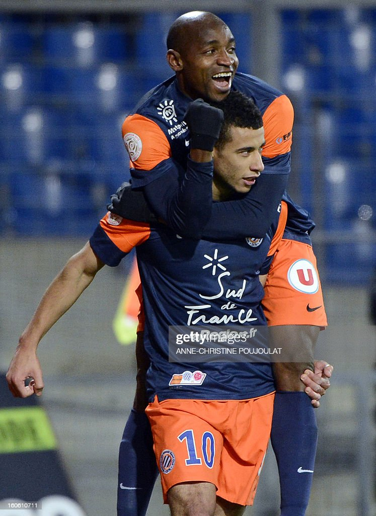 Montpellier's Moroccan midfielder Younes Belhanda (bottom) is congratulated by Senegalese forward Souleymane Camara after scoring a goal during a French L1 football match between Montpellier and Reims on February 3, 2013 at the Mosson stadium in Montpellier, southern France. AFP PHOTO / ANNE-CHRISTINE POUJOULAT